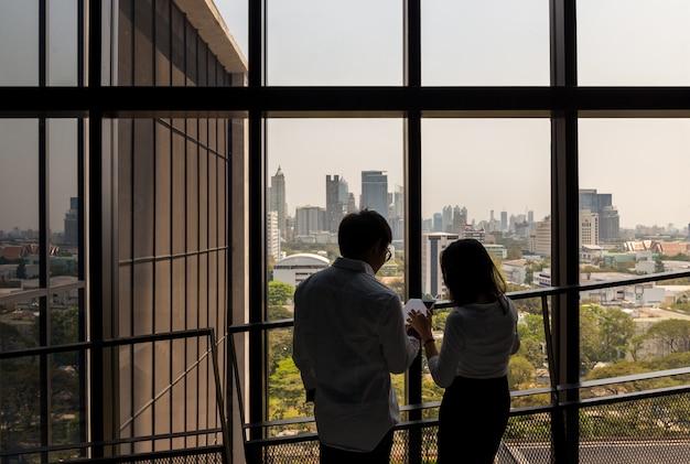 Homme d'affaires et femme travaillent avec le pavé tactile au bureau