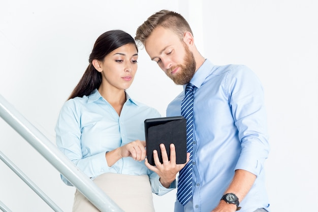 Homme d'affaires et femme utilisant la tablette sur les escaliers