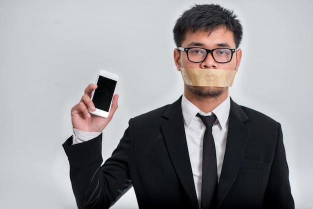 Homme d'affaires fermer la bouche avec smartphone