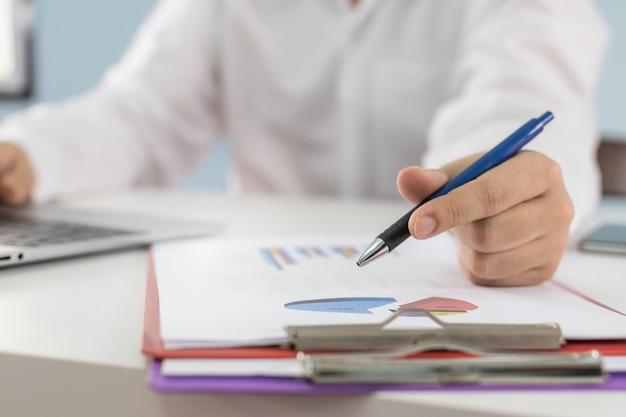 Homme affaires, fonctionnement, et, calculer, sur, finance, à, diagramme graphique, document, rapport, et, ordinateur portable, bureau