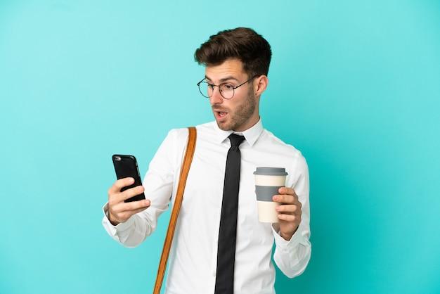 Homme d'affaires sur fond isolé tenant du café à emporter et un mobile