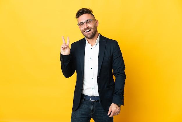 Homme d'affaires sur fond jaune isolé souriant et montrant le signe de la victoire
