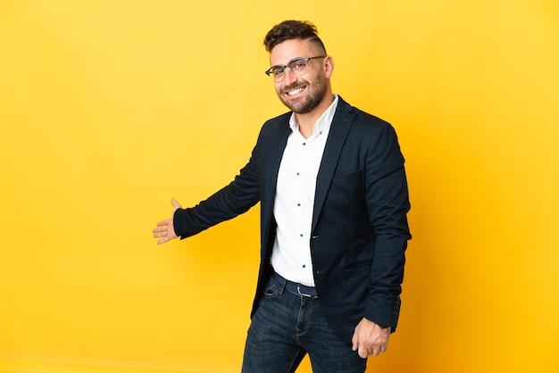 Homme d'affaires sur fond jaune isolé tendant les mains sur le côté pour inviter à venir
