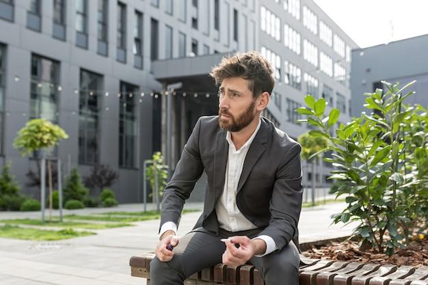 Homme d'affaires fumant une cigarette dans l'air près du bureau soulage le stress après une dure journée de travail, fatigué retravaillé déprimé