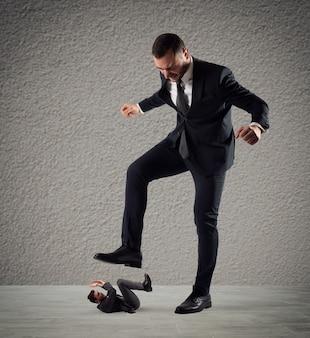 Homme d'affaires furieux qui veut piétiner son employé au bureau