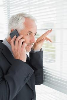 Homme d'affaires furtivement à travers des stores lors d'un appel au bureau