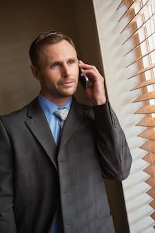 Homme d'affaires furtivement à travers les stores lors d'un appel