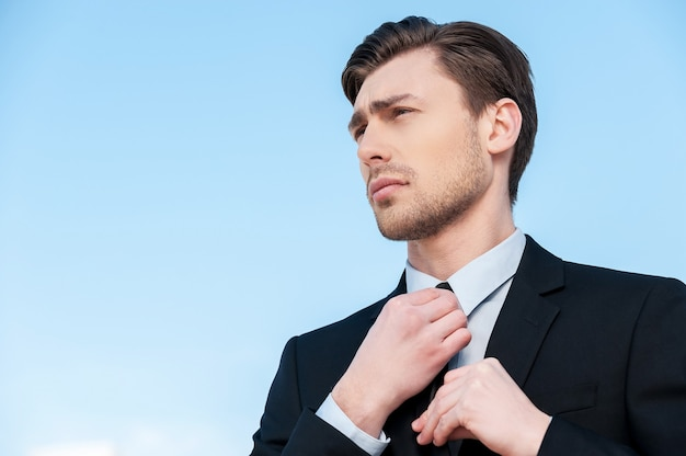 Homme d'affaires gai. beau jeune homme en tenue de soirée ajustant sa cravate et regardant loin