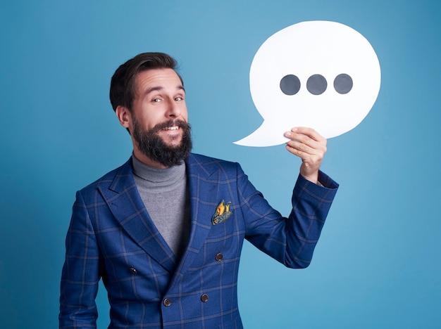 Homme d'affaires gai avec la bulle de dialogue posant