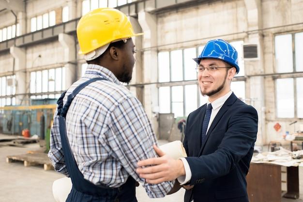 Homme d'affaires gai collaborant avec le directeur de la construction
