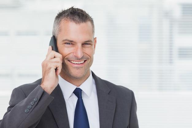 Homme d'affaires gai dans un bureau lumineux en regardant la caméra tout en ayant un appel téléphonique