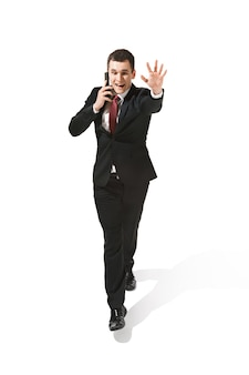 Homme d'affaires gai drôle allant avec un téléphone mobile sur blanc. heureux jeune homme en costume. entreprise, carrière, succès, concept gagnant