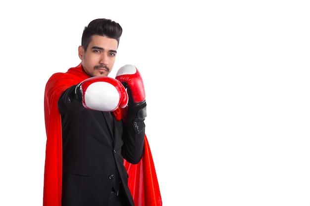Homme d'affaires en gants de boxe et cape rouge de super-héros lève la main à la caméra