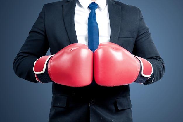 Homme d'affaires avec des gants de boxe rouges avec fond coloré