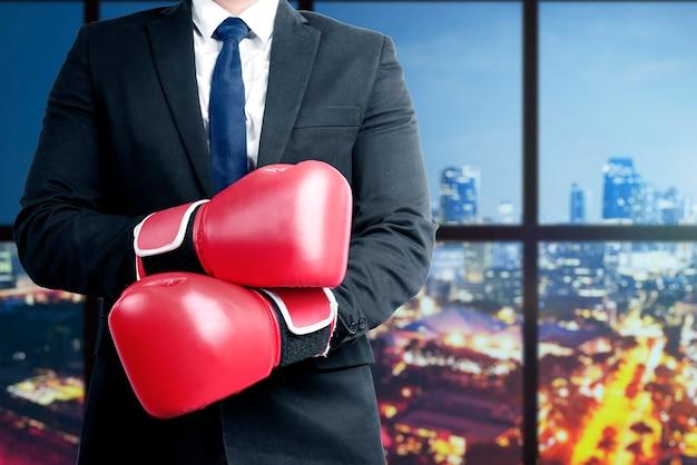 Homme d'affaires avec des gants de boxe rouges avec immeuble de bureaux
