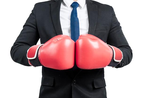 Homme d'affaires avec des gants de boxe rouges isolés sur un mur blanc
