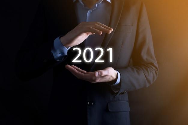 Homme d'affaires avec un geste de protection debout posture main tenant l'inscription 2021