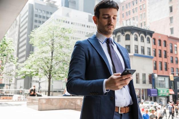 Homme d'affaires grave à l'aide de smartphone dans la rue