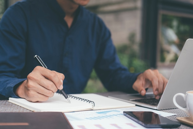 Homme d'affaires gros plan écrit la main et à l'aide d'ordinateur.
