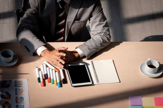 Un homme d'affaires en gros plan en tenue de soirée s'assoit à table avec un téléphone intelligent, du papier document et du café