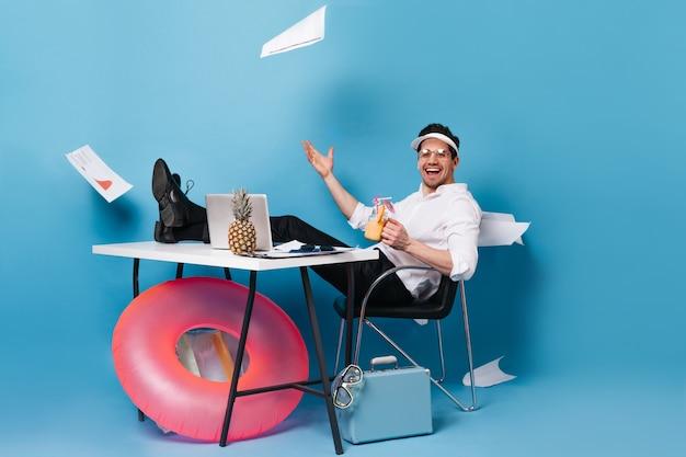 Homme d'affaires guilleret en costume et casquette disperse des graphiques, dégustant un délicieux cocktail, assis à table avec ordinateur portable, anneau en caoutchouc, valise sur l'espace bleu.