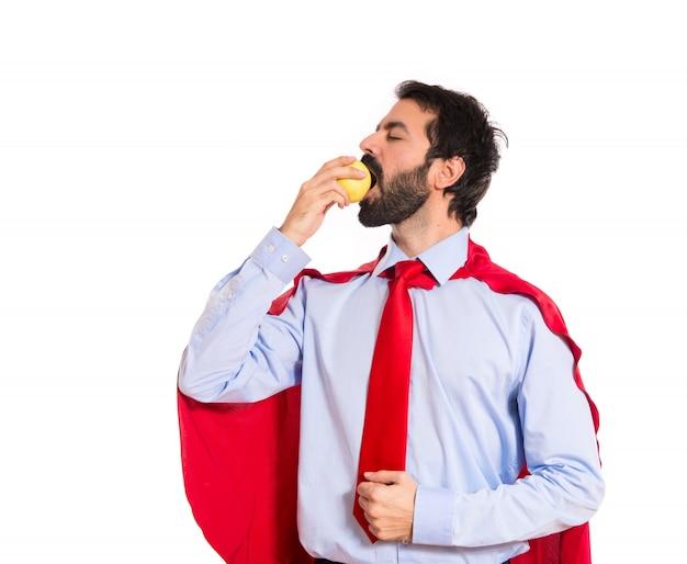 Homme d'affaires habillé comme un super-héros en mangeant une pomme