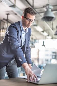 Homme d'affaires habillé de manière décontractée, debout devant une table de café, touchant le clavier d'un ordinateur portable devant lui.