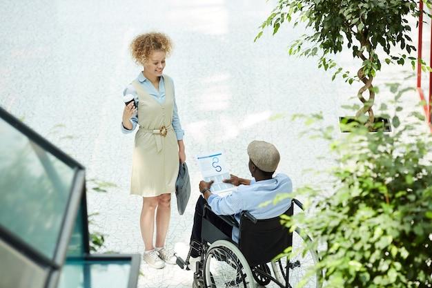 Homme d'affaires handicapé africain assis en fauteuil roulant avec un graphique d'entreprise dans ses mains et en discuter avec la femme d'affaires