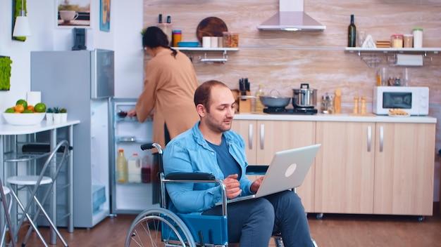 Homme d'affaires handicapé en fauteuil roulant travaillant sur un ordinateur portable pendant que sa femme cuisine dans la cuisine. homme d'entreprise avec paralysie handicap handicap handicapé difficultés à travailler après accident ayant internet