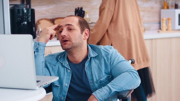 Homme d'affaires handicapé parlant lors d'un appel vidéo sur un ordinateur portable dans la cuisine. femme cuisinant. homme d'entreprise avec paralysie handicap handicap handicapé difficultés à travailler après accident ayant internet