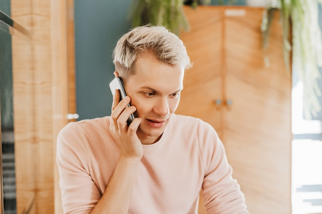 Homme d'affaires heureux assis à la cafétéria avec ordinateur portable et smartphone