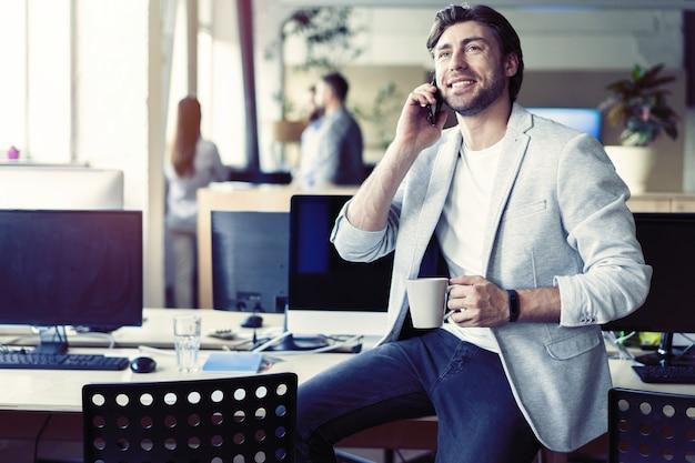 Homme d'affaires heureux ayant parler et boire du café