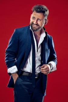 L'homme d'affaires heureux debout et souriant contre le mur rouge