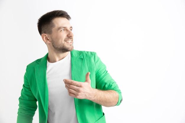 Homme d'affaires heureux debout, souriant isolé sur un espace gris. beau portrait mâle demi-longueur. jeune homme satisfait