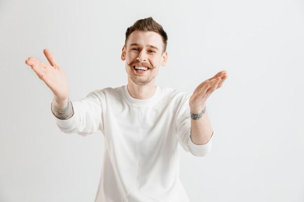 Homme d'affaires heureux debout, souriant isolé sur fond gris studio. beau portrait mâle demi-longueur. jeune homme satisfait. émotions humaines, concept d'expression faciale.