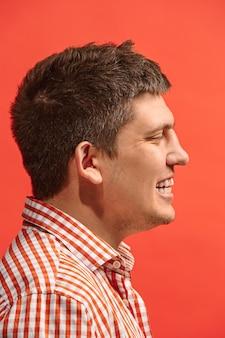 Homme d'affaires heureux debout et souriant isolé sur studio rouge.
