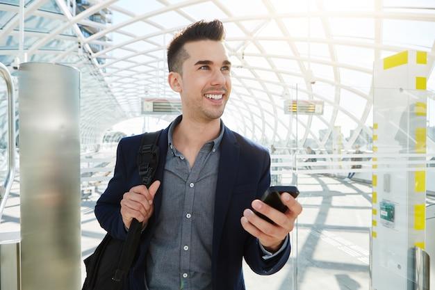 Homme d'affaires heureux en gare avec téléphone portable