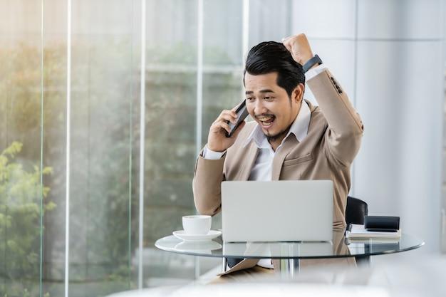 Homme d'affaires heureux parler au téléphone mobile et à l'aide d'un ordinateur portable