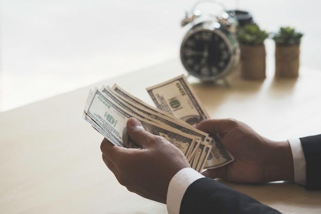 Homme d'affaires heureux et réussi tenant dans la main des billets d'un dollar américain.