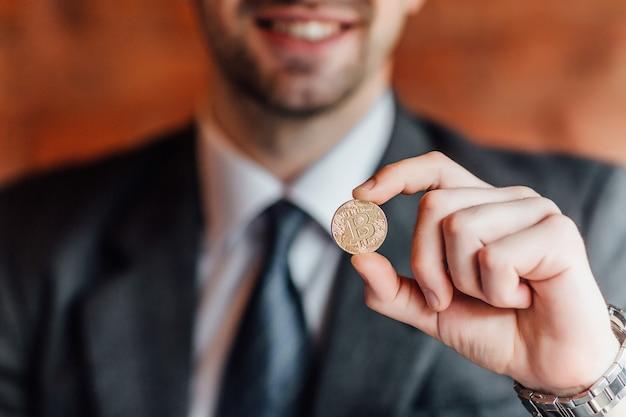 Un homme d'affaires heureux tient un bitcoin dans une main sur un mur orange