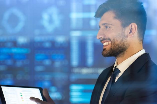 L'homme d'affaires heureux tient une tablette sur le fond d'écran virtuel