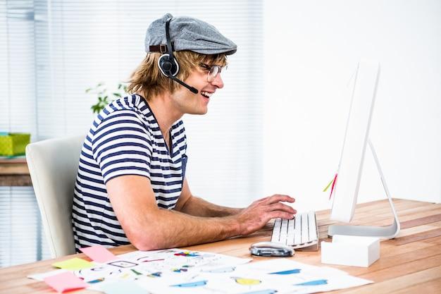 Homme d'affaires hipster souriant à l'aide de casque dans son bureau