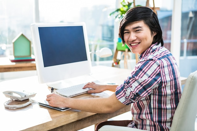 Homme d'affaires hipster souriant à l'aide d'ordinateur de bureau