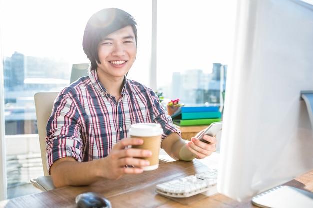 Homme d'affaires hipster souriant à l'aide de smartphone au bureau