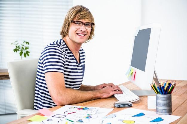 Homme d'affaires hipster souriant à l'aide de son ordinateur de bureau
