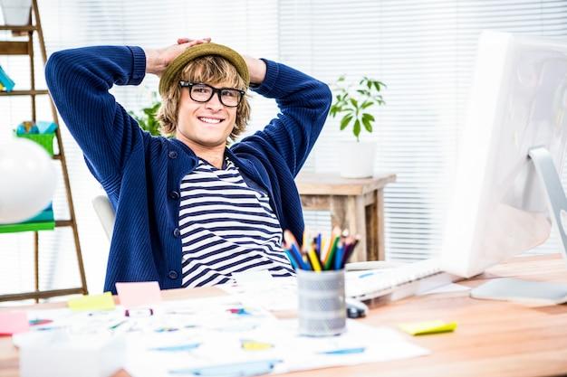 Homme d'affaires hipster souriant prend une pause dans son bureau
