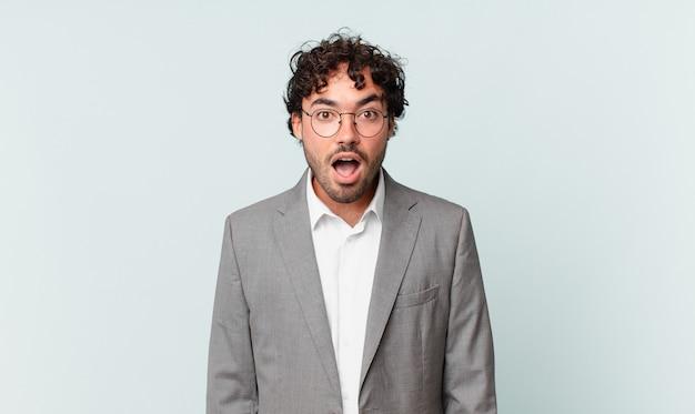 Homme d'affaires hispanique ayant l'air très choqué ou surpris, regardant la bouche ouverte en disant wow