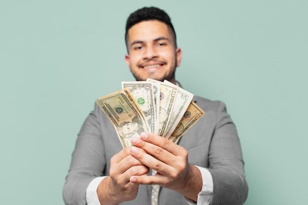 Homme d'affaires hispanique expression heureuse et tenant des billets en dollars