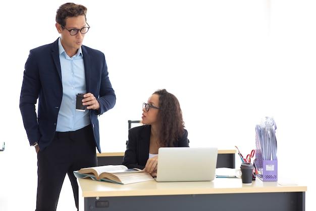 Homme d'affaires hispanique et femme d'affaires se reposant, parlant et buvant du café dans un bureau à domicile moderne. équipe professionnelle de gens d'affaires à succès.