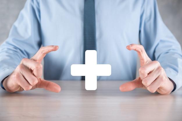 Homme d'affaires, l'homme en main offre une chose positive telle que le profit, les avantages, le développement, la rse représentée par le signe plus